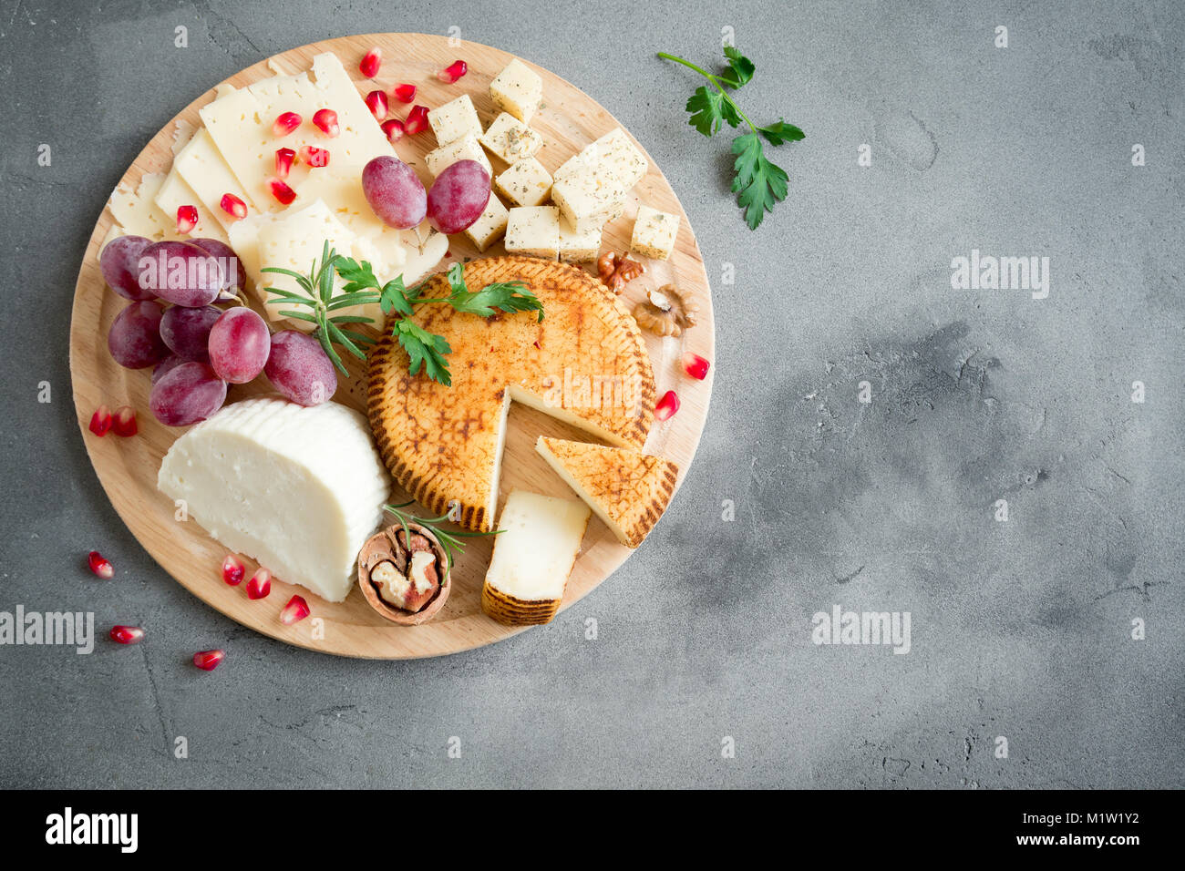 Cheese platter with assorted cheeses, grapes, nuts over gray stone background, copy space. Italian cheese and fruit Stock Photo