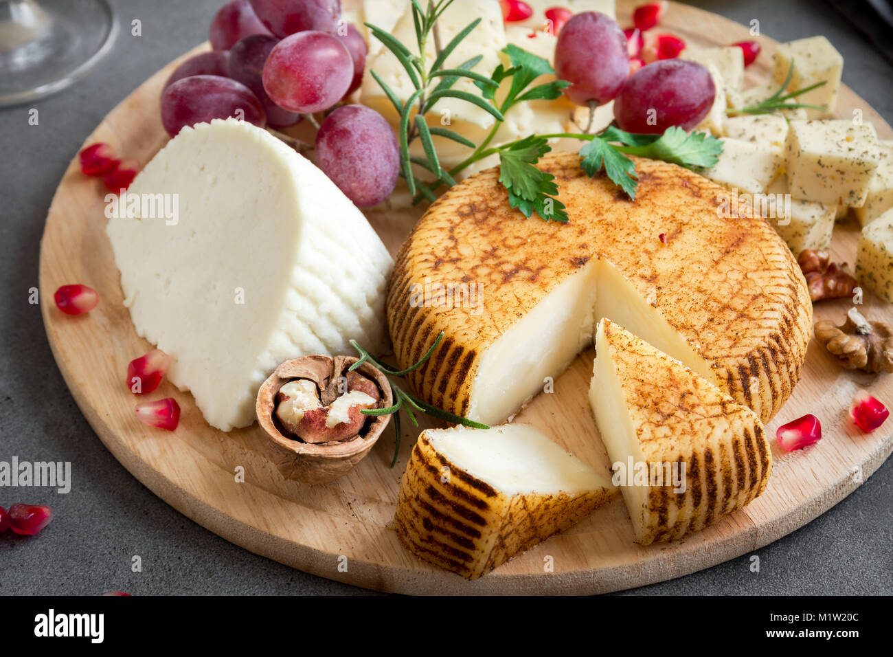 Cheese platter with assorted cheeses, grapes, nuts over gray stone background, copy space. Italian cheese and fruit - Stock Image