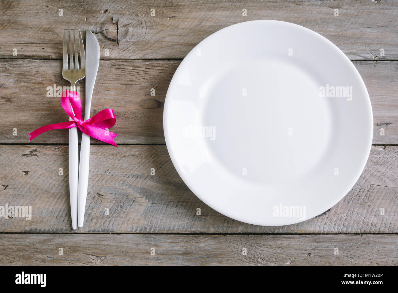 Romantic table setting with white plate, modern cutlery and red ...