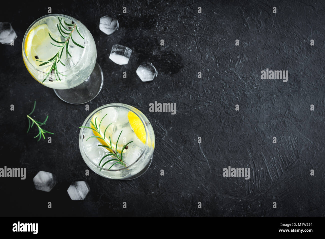 Alcohol drink (gin tonic cocktail) with lemon, rosemary and ice on rustic black stone table, copy space, top view. Stock Photo