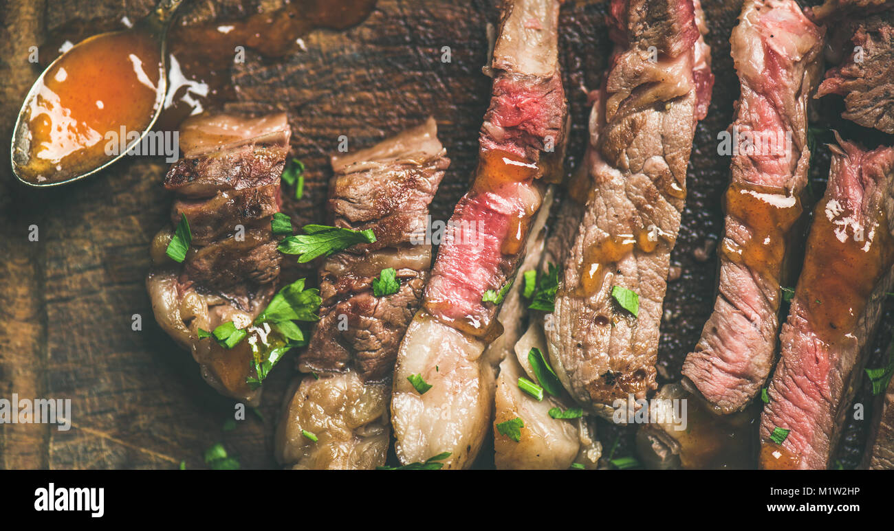 Flat-lay of grilled ribeye beef steak cut into peices - Stock Image