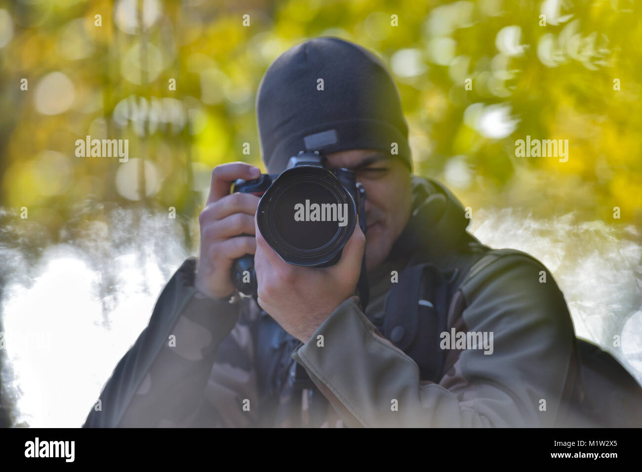 Wildlife, nature man photographer in camouflage outfit shooting, taking pictures - Stock Image