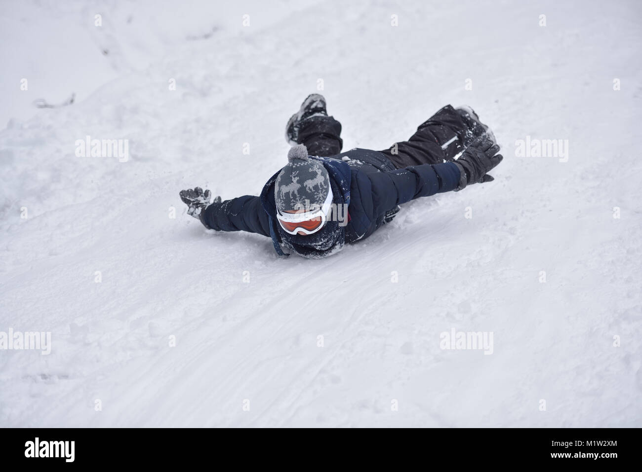 Little boy slides on snow in winter time Stock Photo