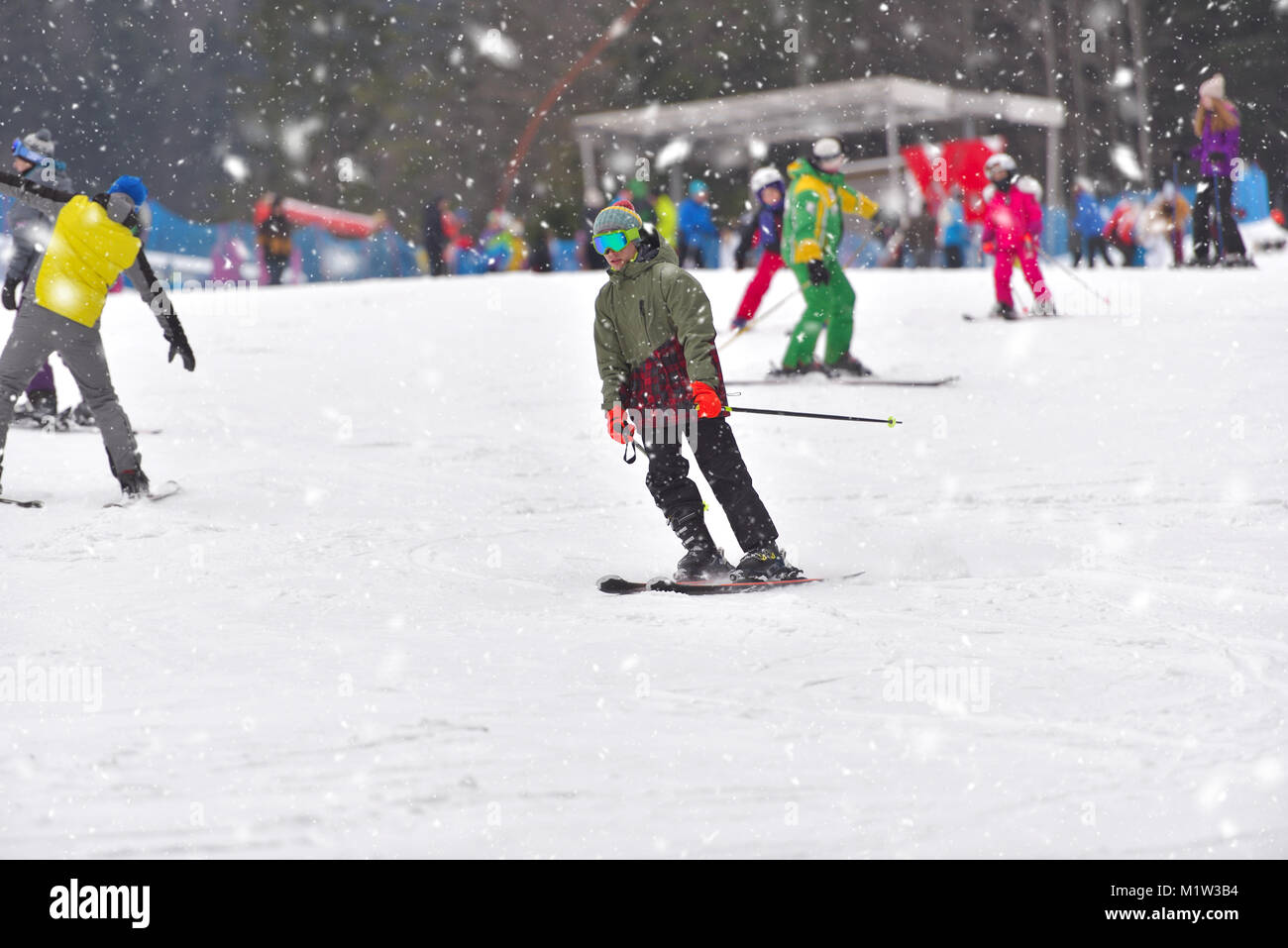 Young man on skiing downhill with people in the background, snowy day - Stock Image