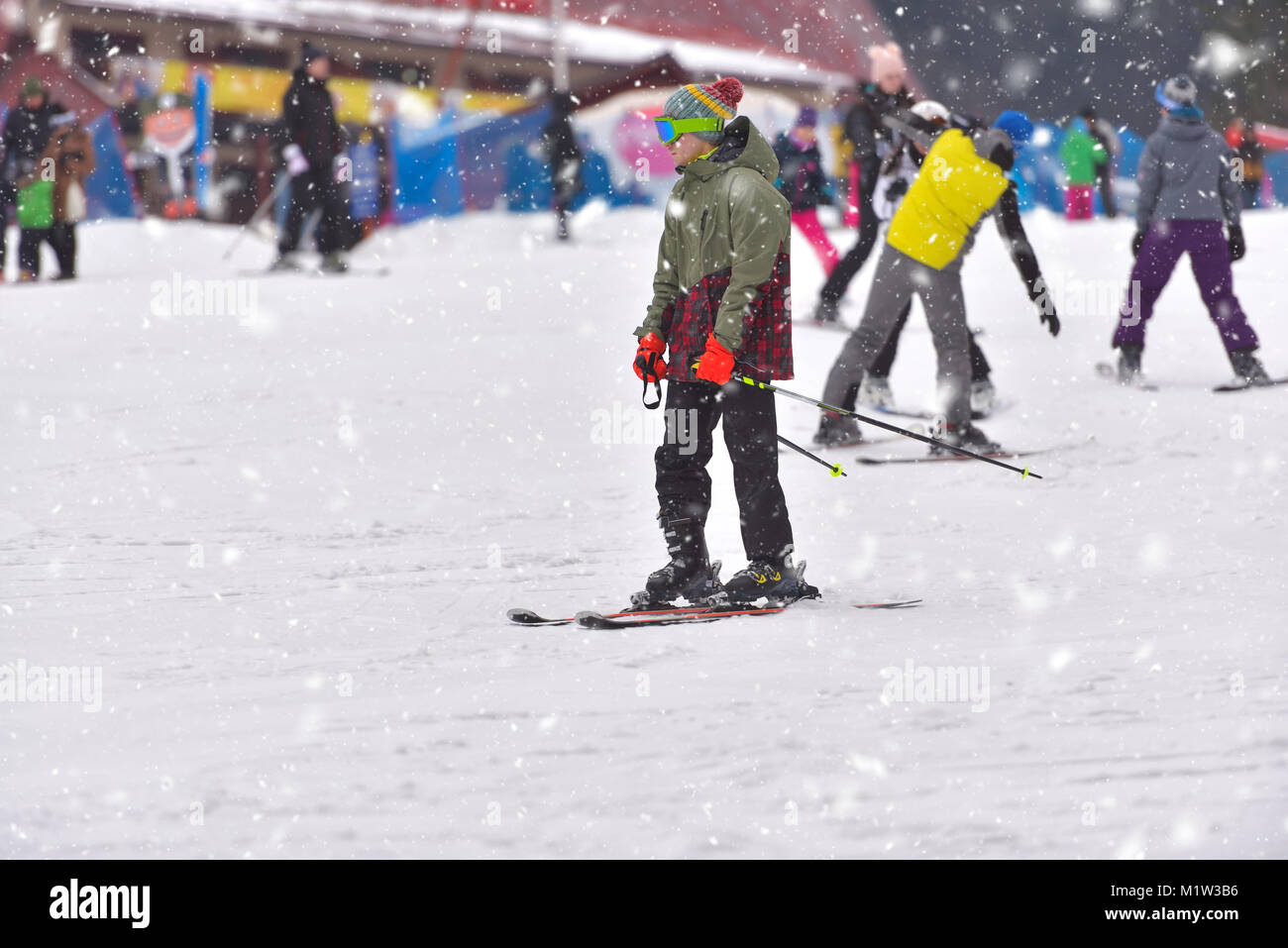 Young man skiing downhill with people in the background, snowy day - Stock Image