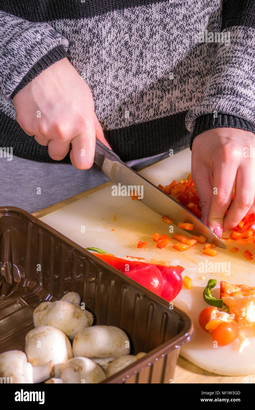 A woman (hands only) chopping a red pepper with a large, sharp, stainless steel kitchen knife. on a plastic chopping - Stock Image