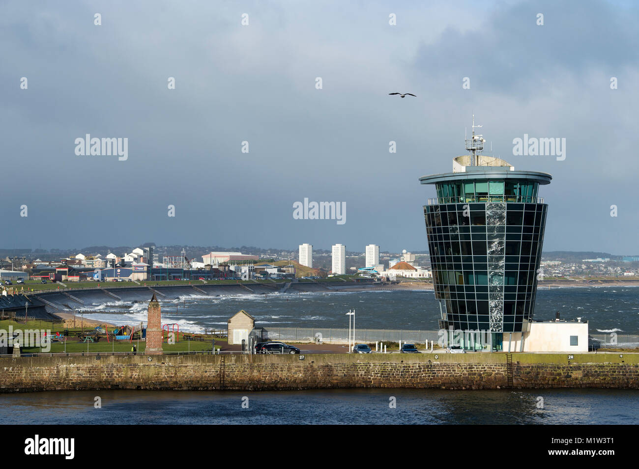 Harbour master's control tower at the entrance to port with beach on North Sea coast. Aberdeen, Aberdeenshire, - Stock Image
