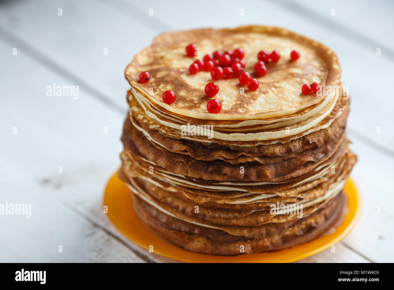 High stack of classic Russian thin pancakes with red currant. Rustic style. Traditional for the Russian pancake - Stock Image