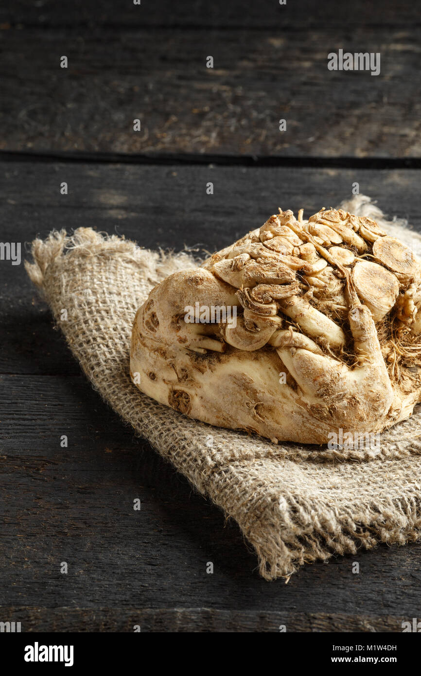 celery root and burlap on dark wooden background. - Stock Image