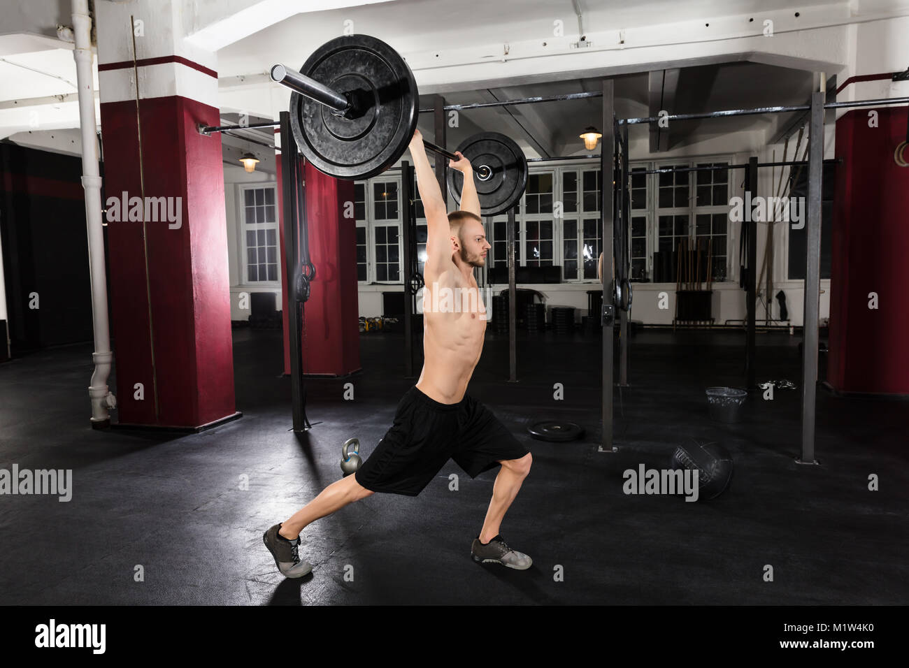 Young Athlete Man Working Out With Barbell In The Gym - Stock Image
