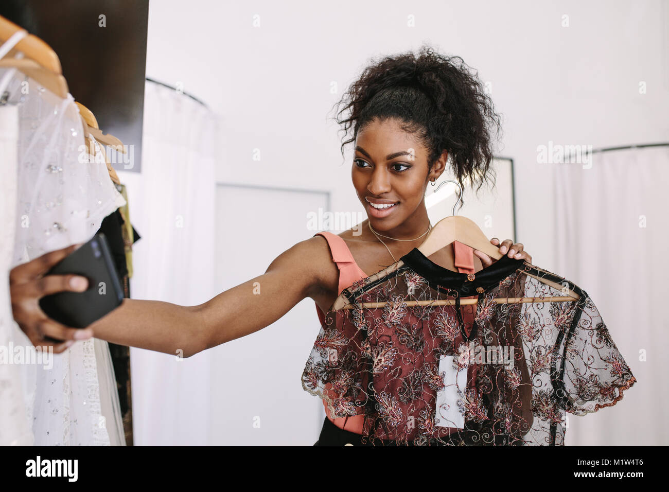 Close up of a fashion designer taking a selfie with a designer dresses in her fashion studio. Customer taking a - Stock Image