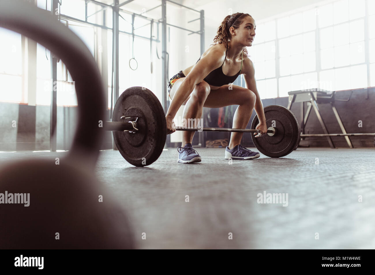 1d56537a4edf Young woman lifting a barbell at the gym. Fit female athlete exercising  with heavy weights