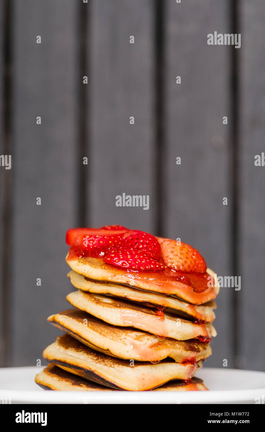 Delicious Strawberry Pancakes on a dark moody background, stunning breakfast with vibrant colors, white plate - Stock Image