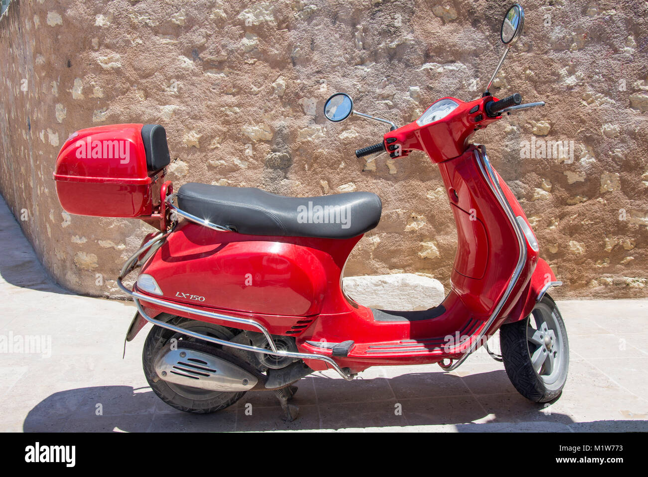 A red Vespa LX 150 scooter parked by wall, Old town, Rethymnon (Rethimno), Rethimno Region, Crete (Kriti), Greece Stock Photo