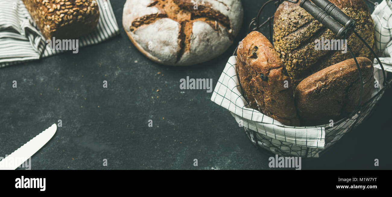 Various bread loaves on grey concrete background, copy space - Stock Image