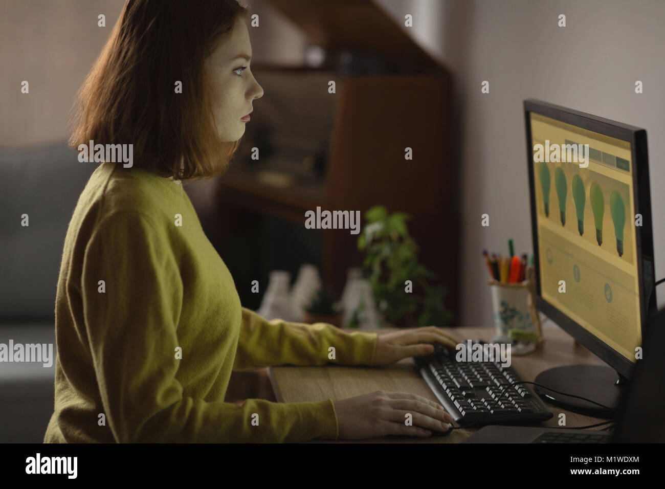 Woman using personal computer at home - Stock Image