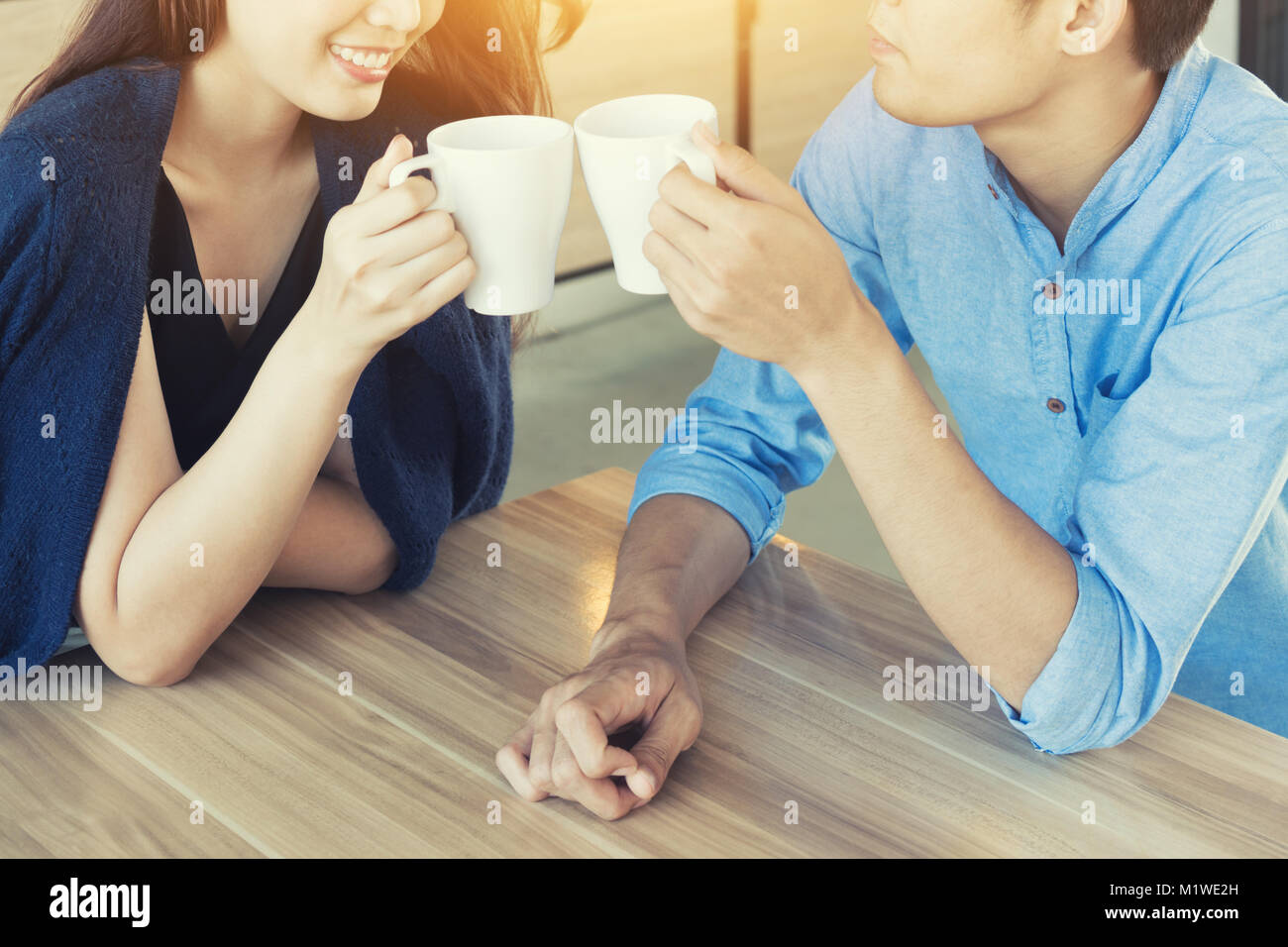 Happy young couple people relaxing meeting and drinking tea or coffee in cafe. Looking happy dating. Stock Photo