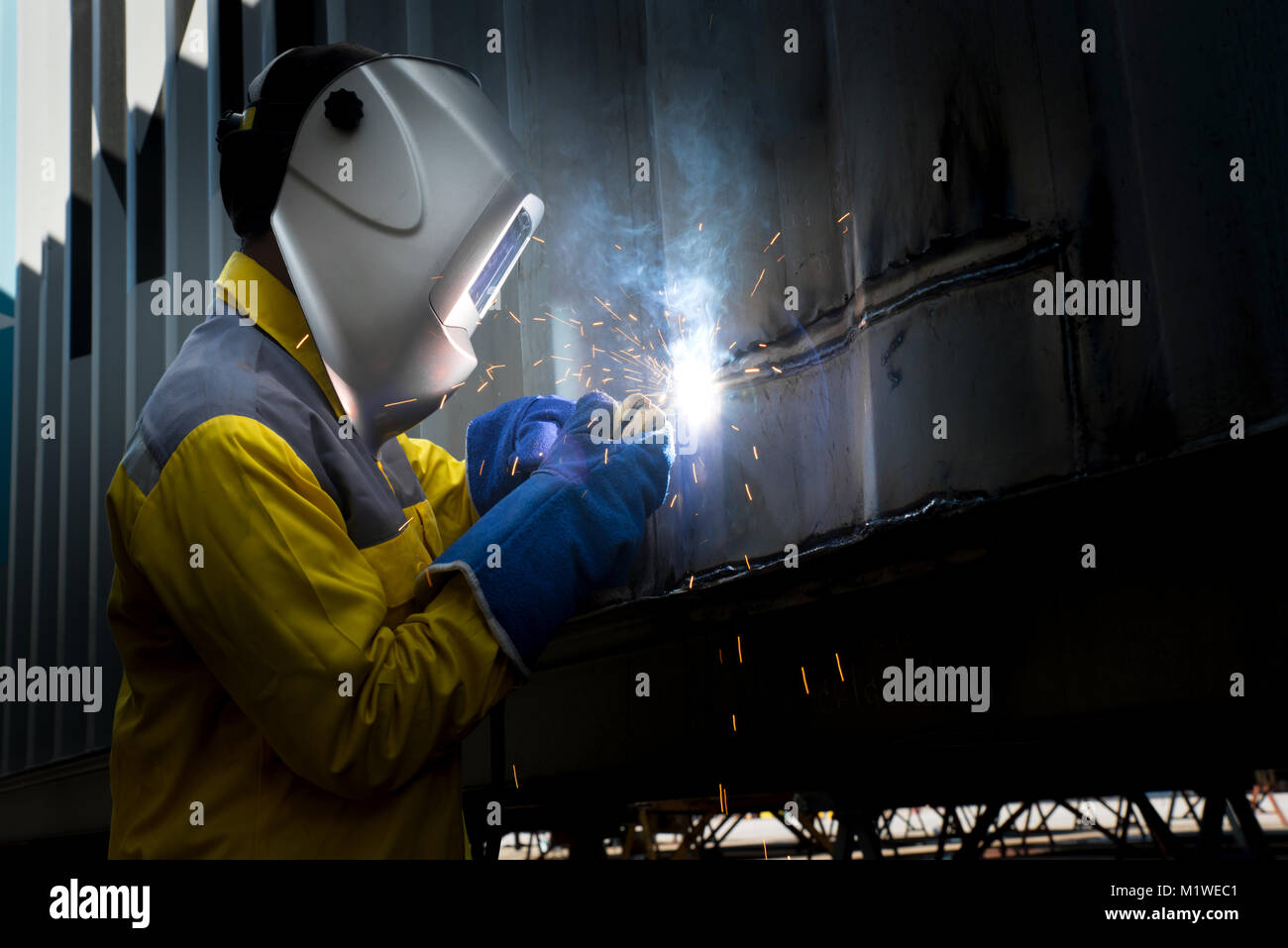 Industry worker with welding steel to repair container structures manufacture workshop. Container maintenance industry. - Stock Image
