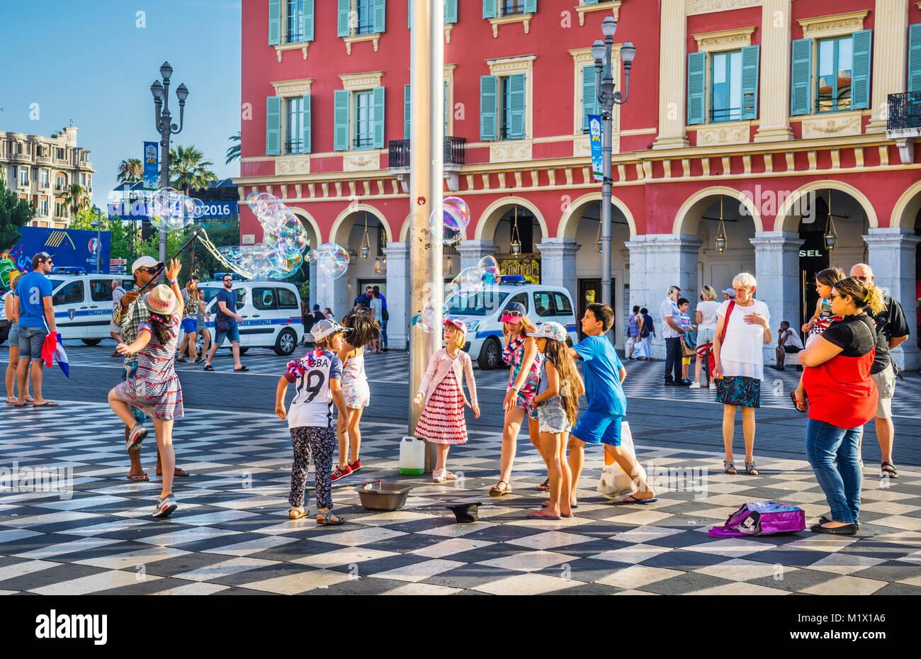 France, Alpes-Maritimes department, Côte d'Azur, Nice, soap bubble fun on historic Place Masséna with - Stock Image