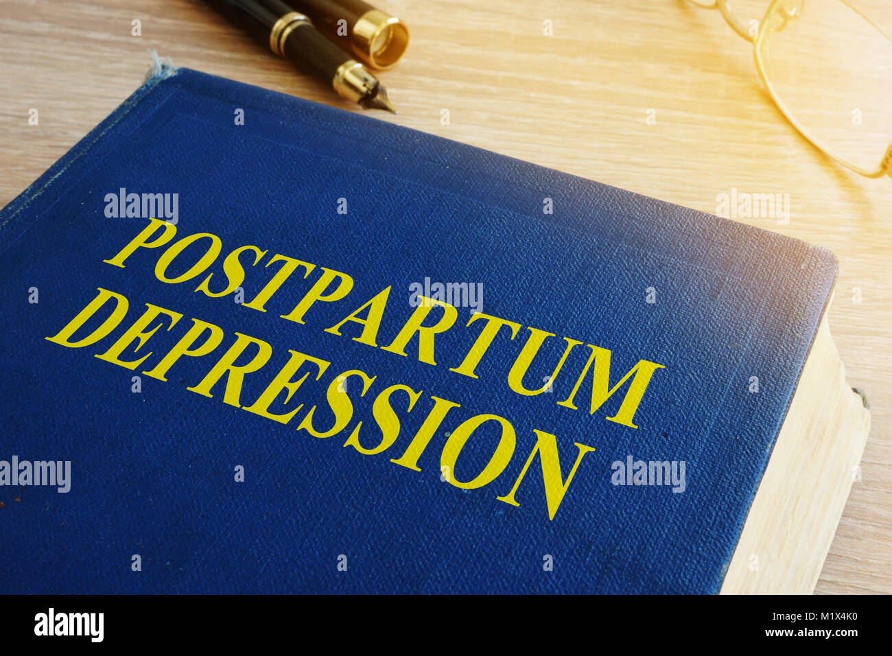 Book with title Postpartum depression on a table. - Stock Image