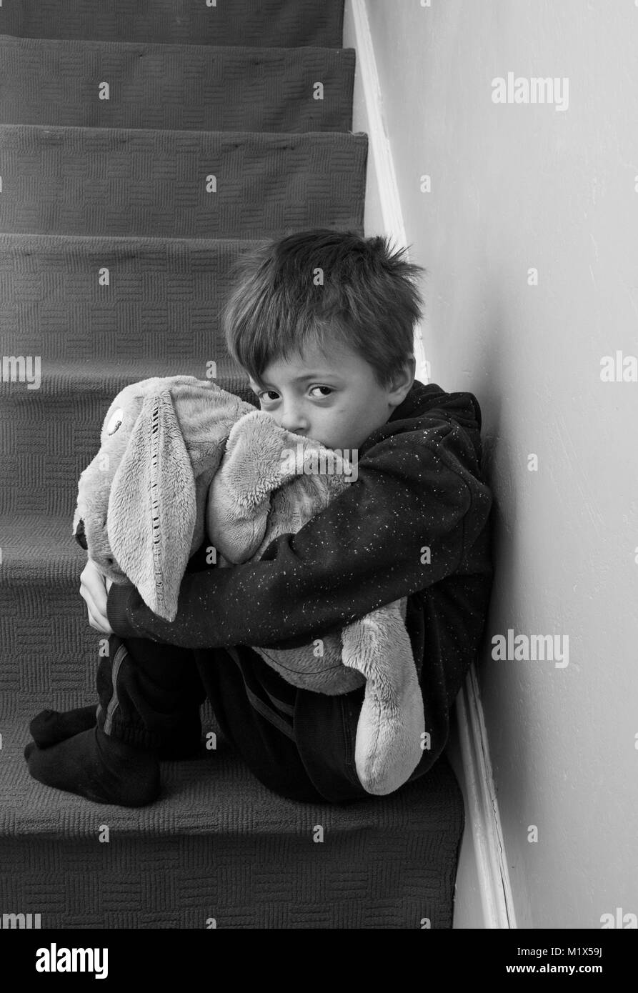 Lonely child feeling abandoned sitting on the stairs stock image