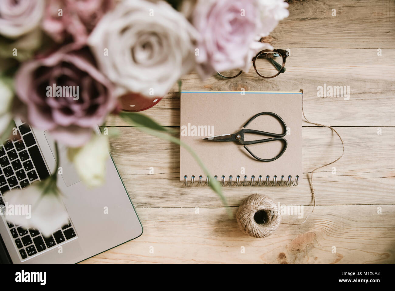 Crafting scissors, cardboard notebook, twine,laptop and flower bouquet on the old rustic table background - Stock Image