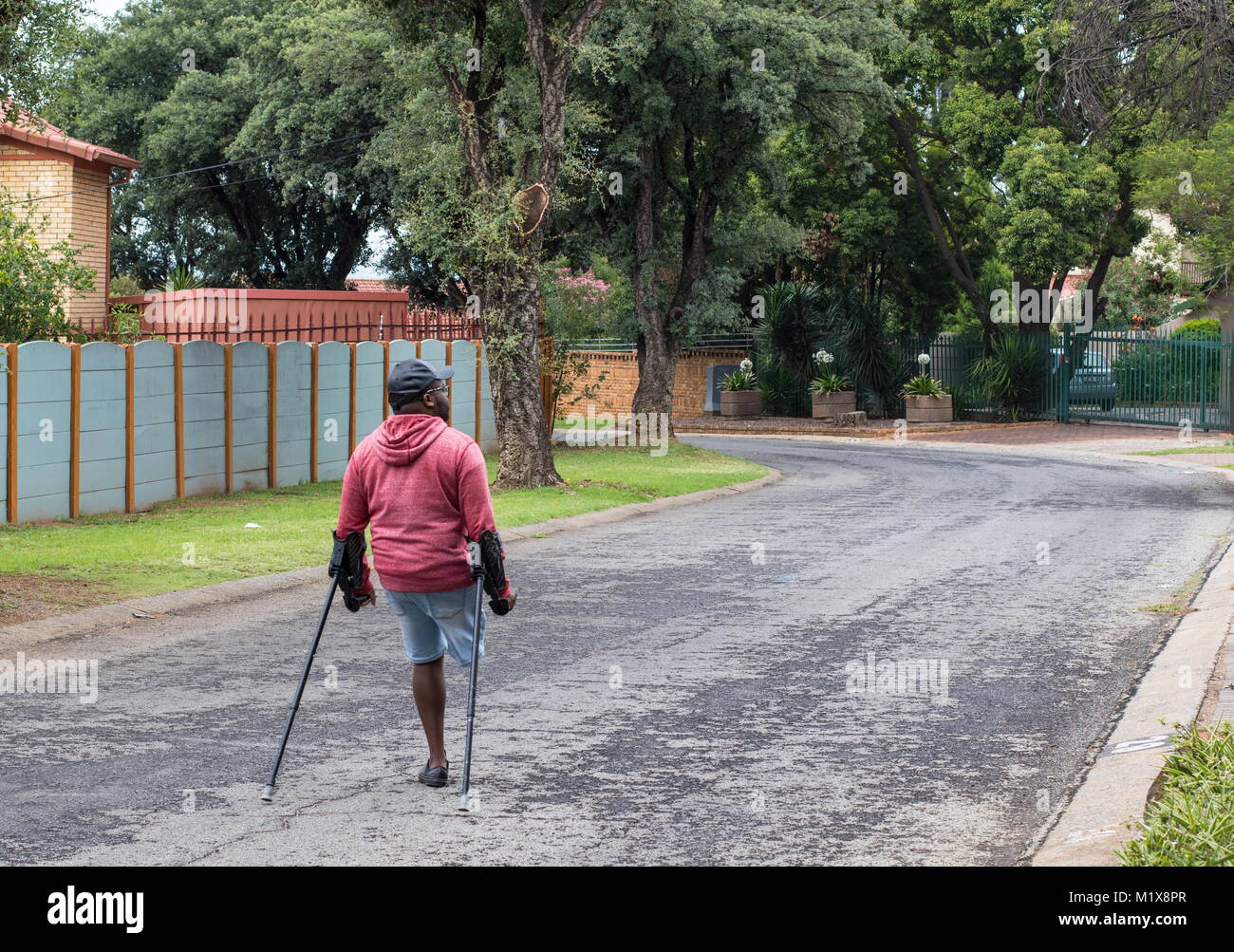 Johannesburg, South Africa - unidentified physically disabled man on crutches struggle through the streets of the - Stock Image