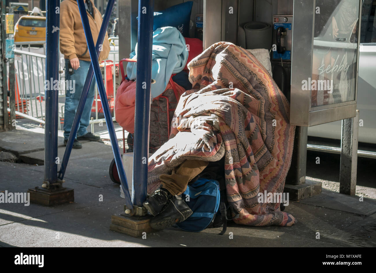 A homeless individual sleeps in front of a pay telephone kiosk in New York on Wednesday, January 31, 2018. (© - Stock Image