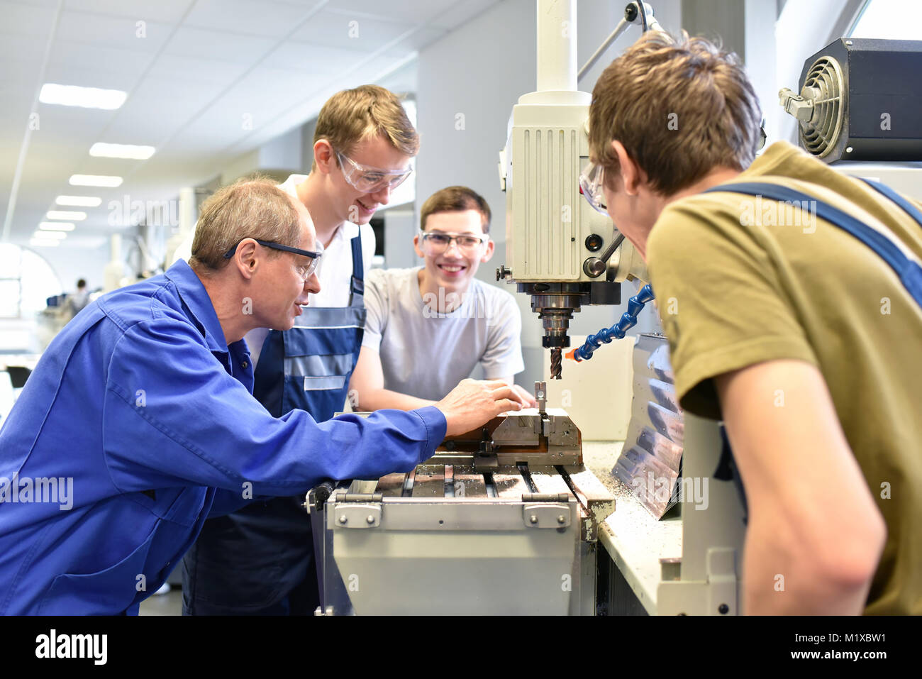 Group of young people in technical vocational training with teacher - Stock Image