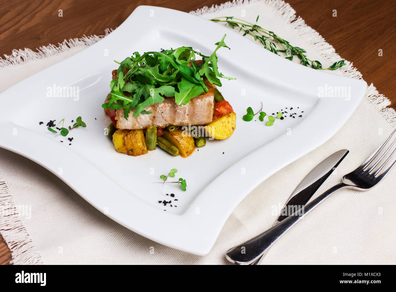 Baked fish fillets with potatoes and green beans on a square plate - Stock Image
