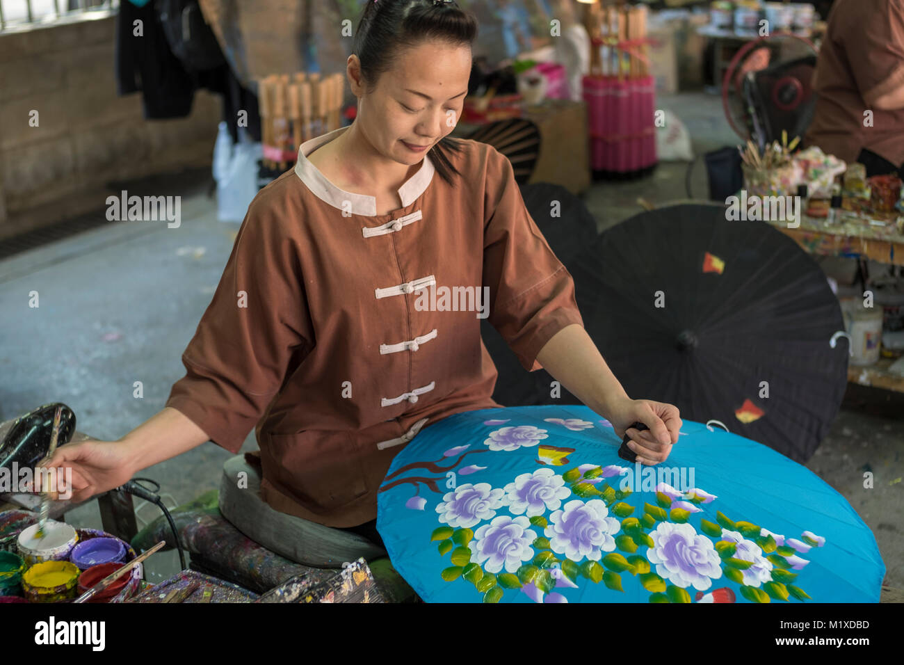 A Thai craftswoman making traditional umbrella at Umbrella Making Centre in Bo Sang Handicraft Centre on San Kamphaeng - Stock Image