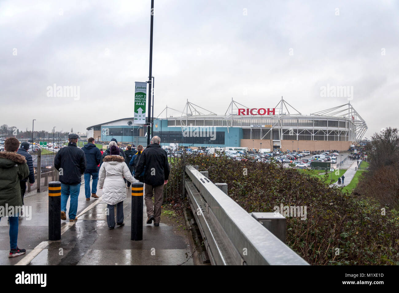 Rugby union supporters walk towards Ricoh Stadium, Coventry, UK home of Wasps professional rugby team - Stock Image