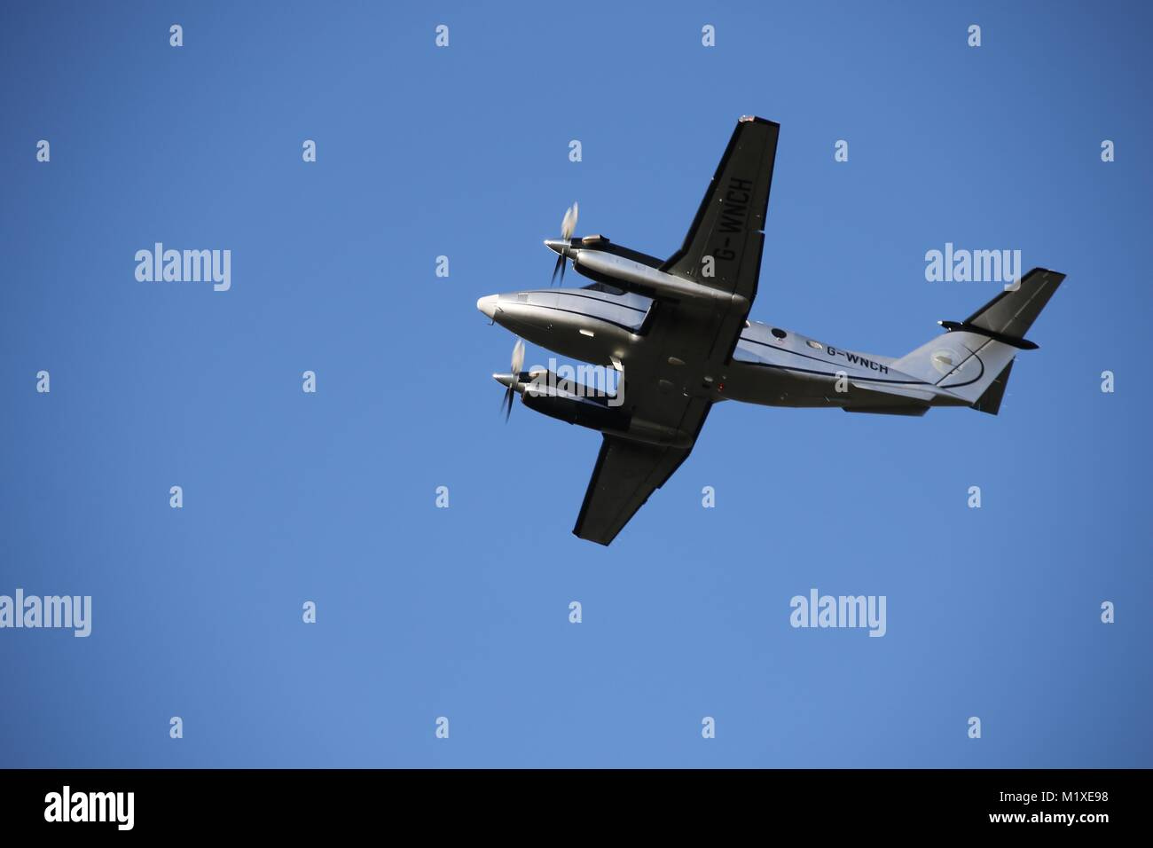 A small twin engine plane in a blue sky shortly after taking off from Fairoaks Airport near Woking, Surrey - Stock Image