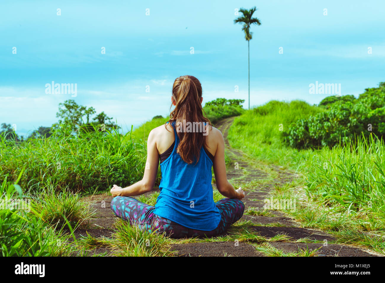 Woman meditates in yoga asana Padmasana - Stock Image