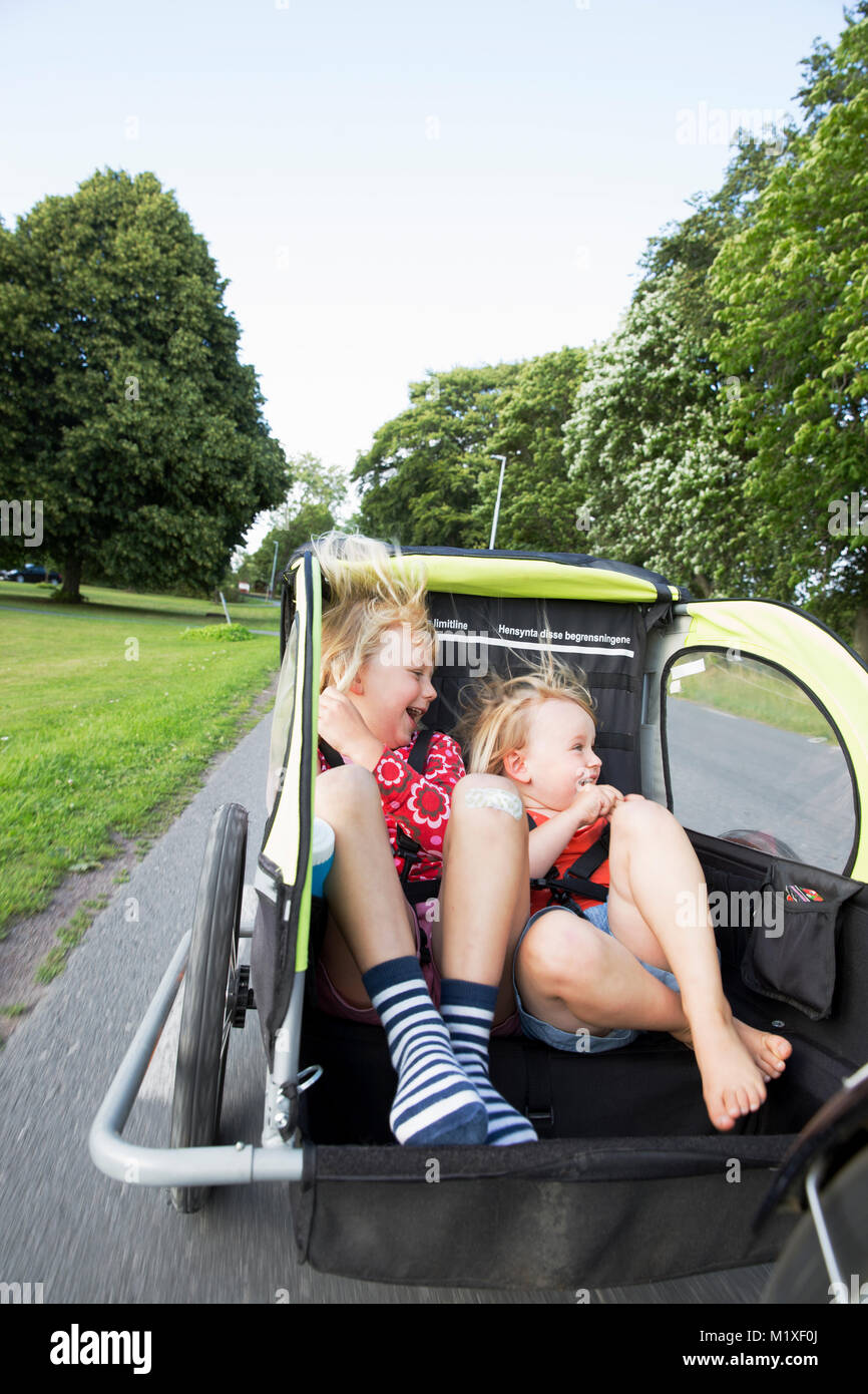 Sisters in bicycle trailer in Smaland, Sweden - Stock Image