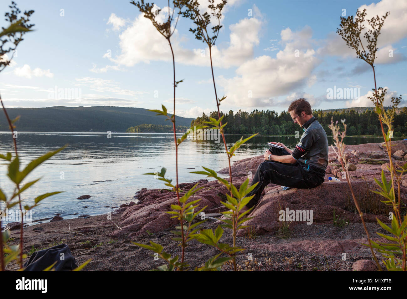 Young man on riverbank in High Coast, Sweden - Stock Image