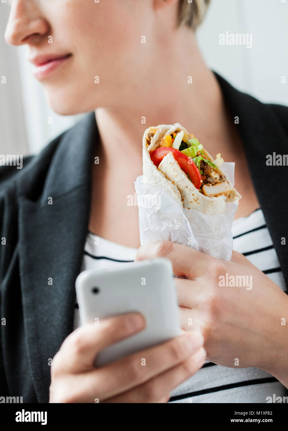 Mid adult woman holding chicken tortilla - Stock Image