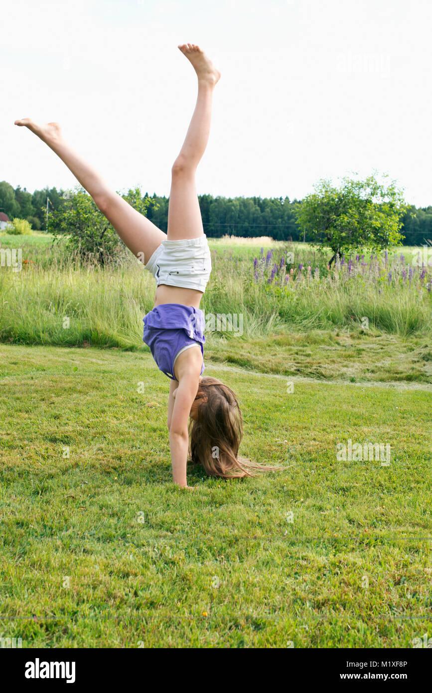 Girl doing cartwheel in Kallandso, Sweden - Stock Image