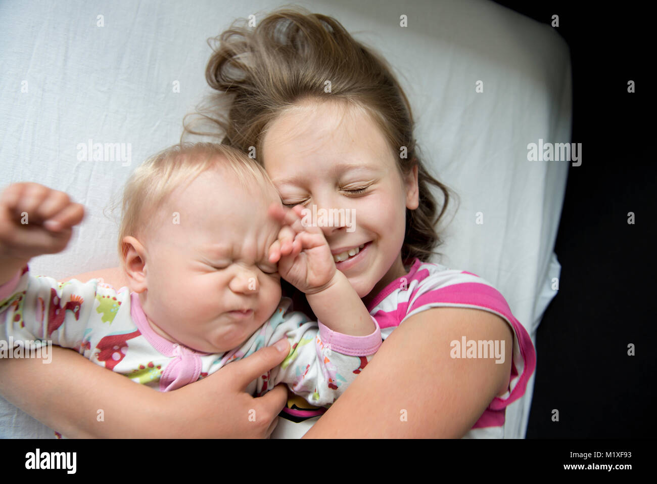 Girl lying down with her baby sister in Sweden - Stock Image