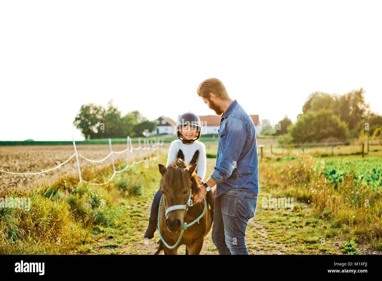 Man helping his daughter ride horse in Friseboda, Sweden - Stock Image