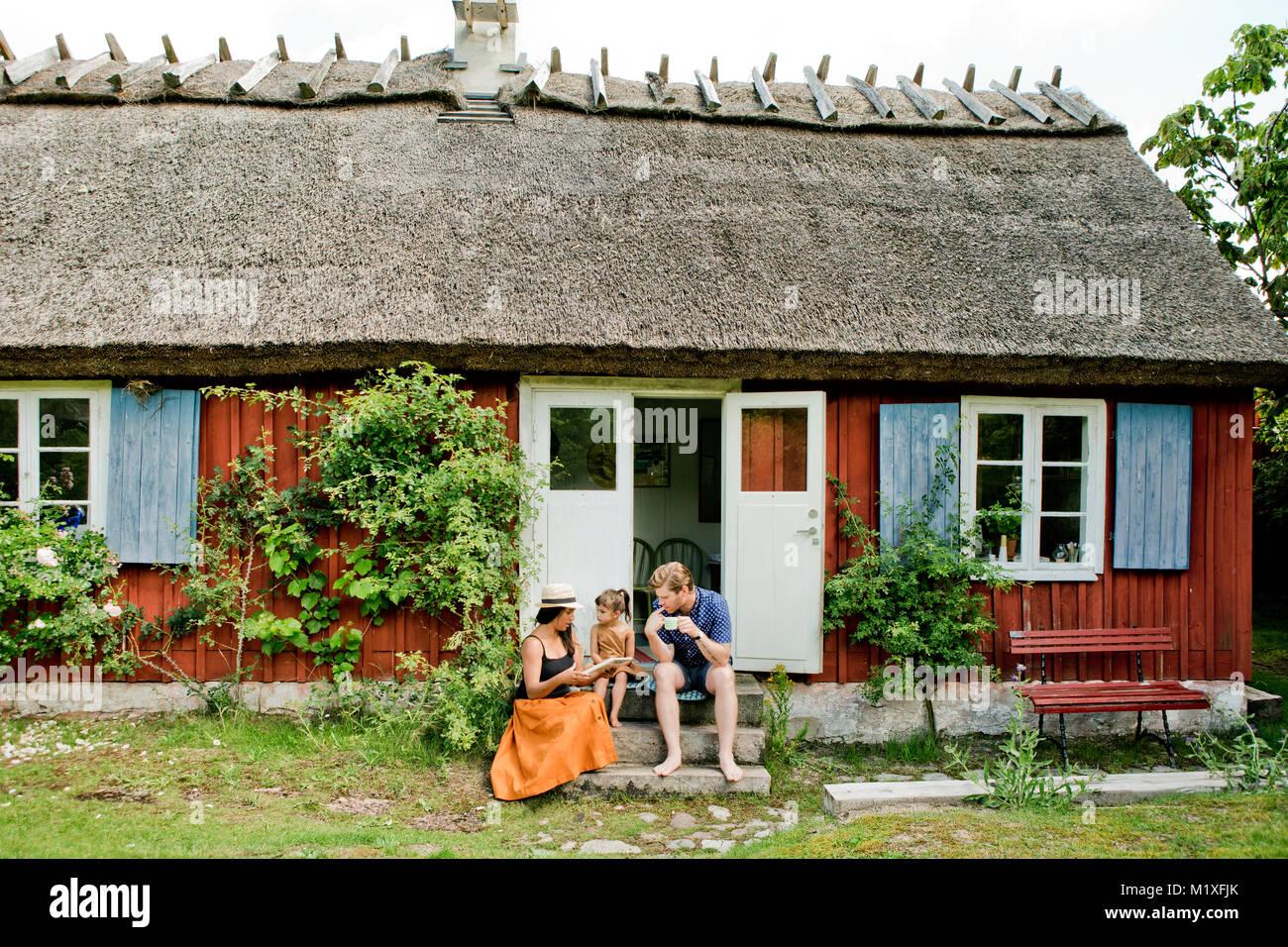 Family sitting on steps in Friseboda, Sweden - Stock Image