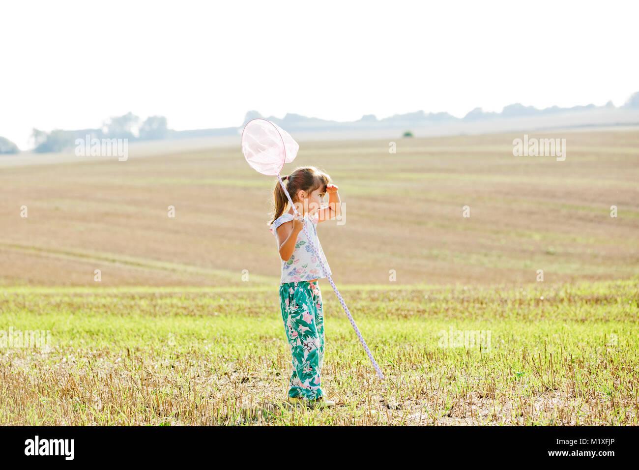 Girl with bug net in field in Friseboda, Sweden - Stock Image
