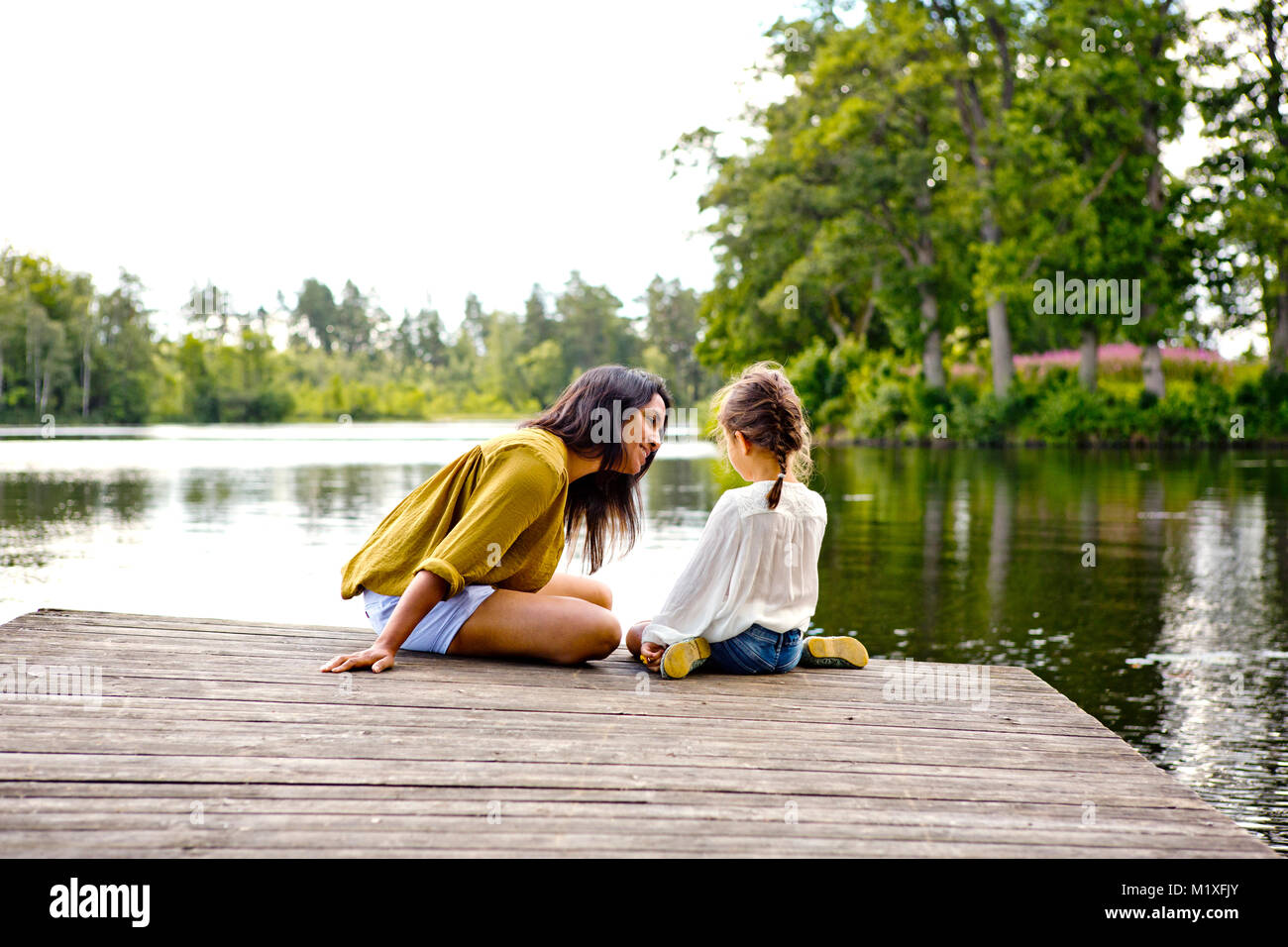 Mother and daughter on pier beside lake in Friseboda, Sweden - Stock Image
