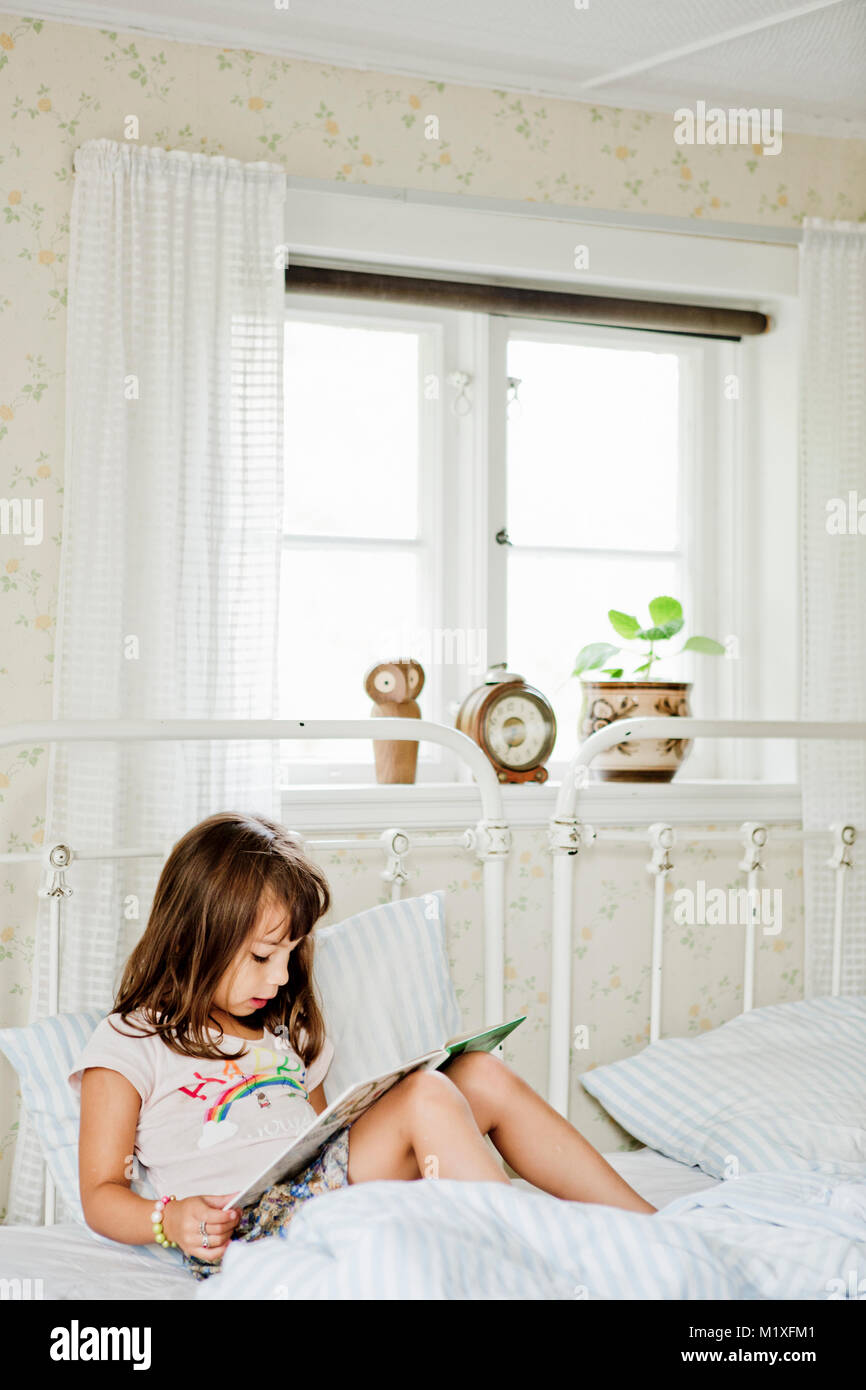 Girl reading in bed - Stock Image