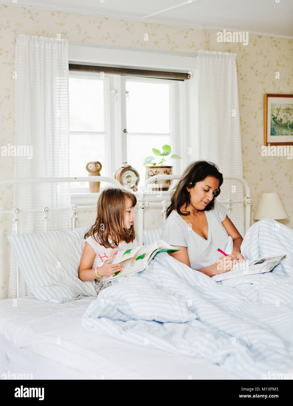 Mother and daughter reading in bed - Stock Image