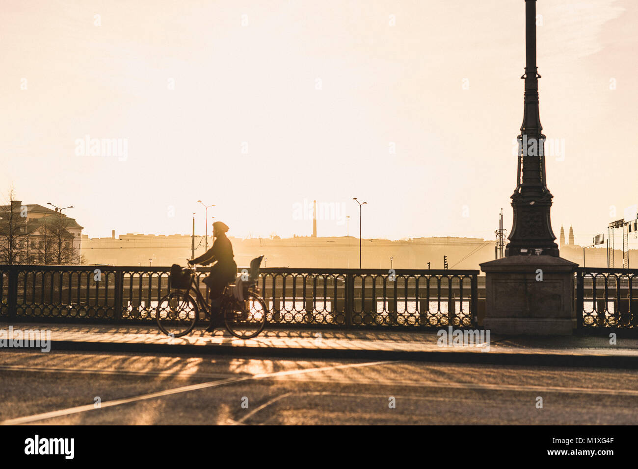 Woman bicycling along bridge in Stockholm, Sweden - Stock Image