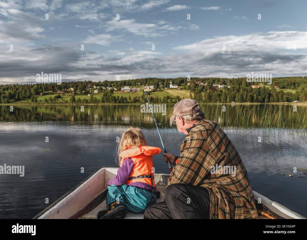 Grandfather and granddaughter fishing Borgvattnet, Sweden - Stock Image