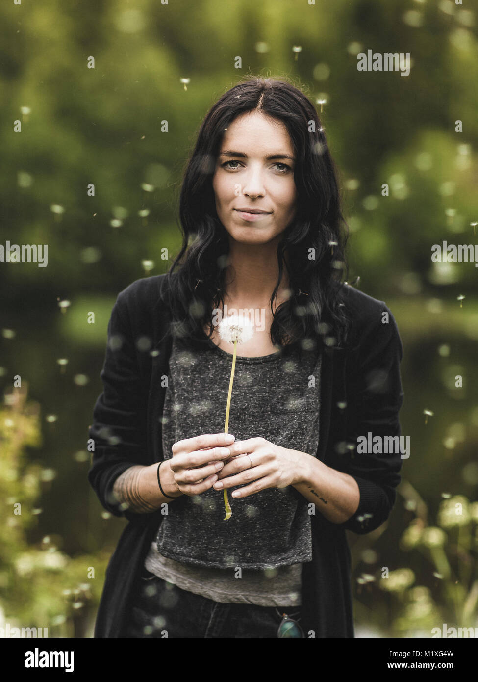 Young woman with dandelion in Sweden - Stock Image