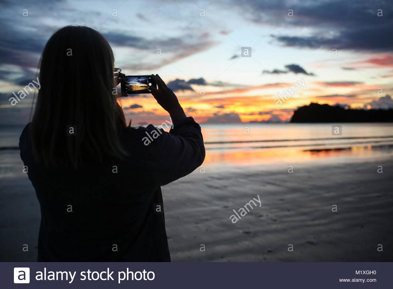 Woman taking photograph of beach during sunset in Ko Lanta, Thailand - Stock Image