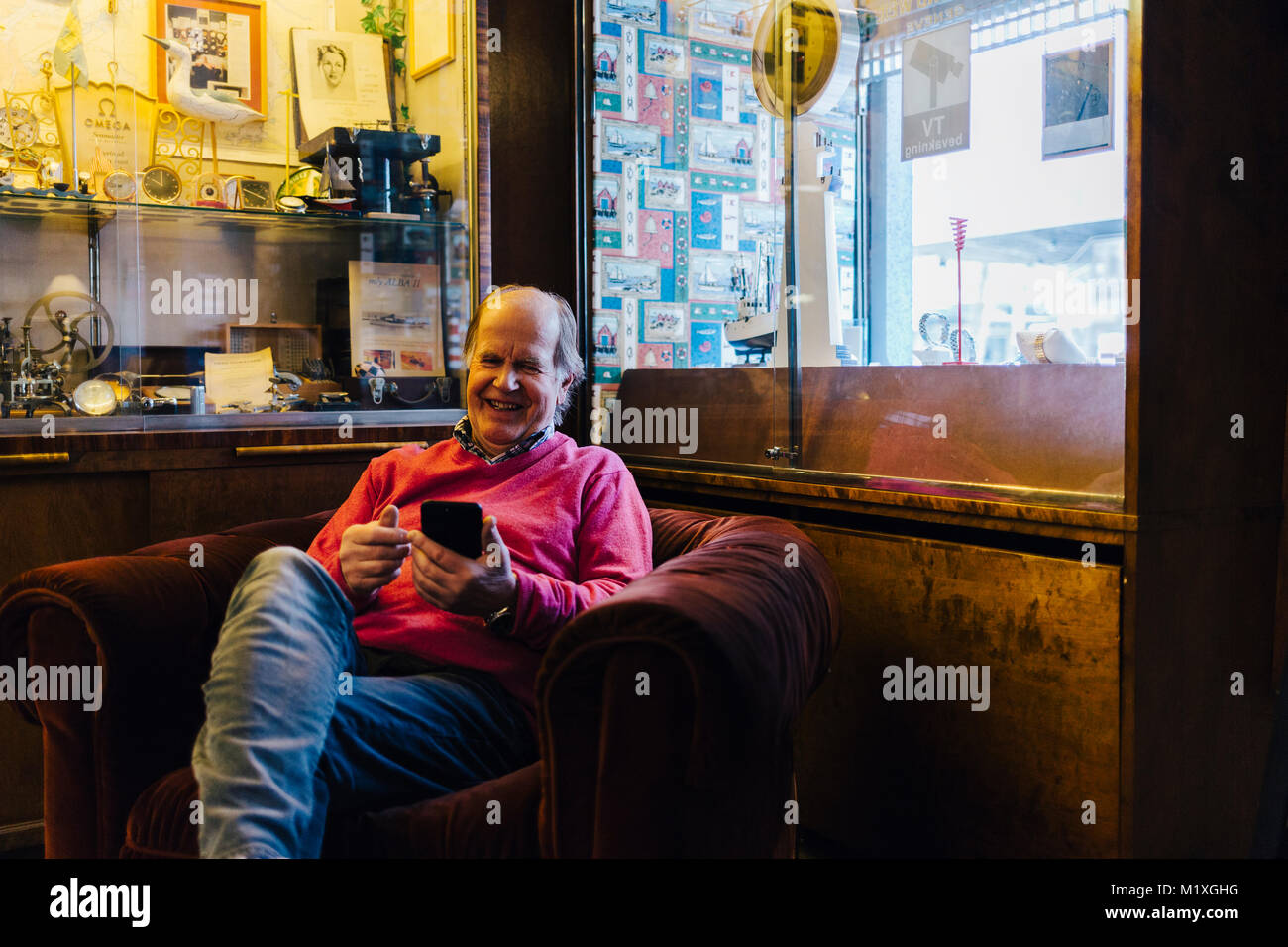 Man in armchair with smart phone in Sweden - Stock Image